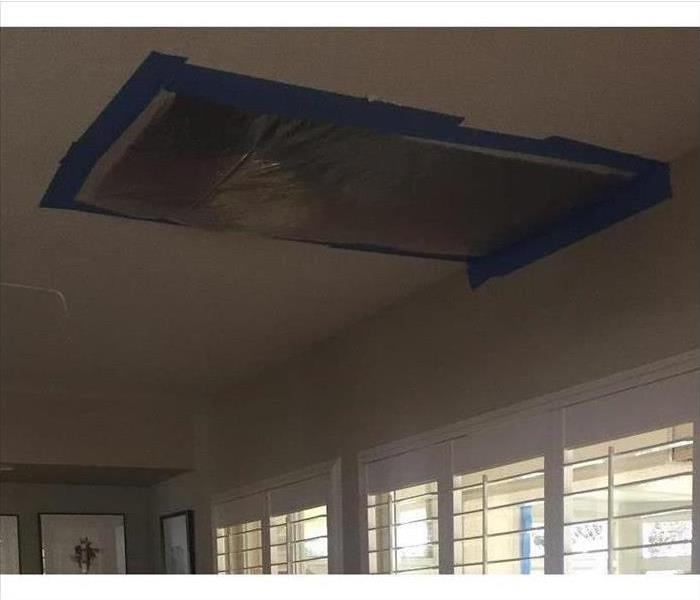 Ceiling with large rectangular removed. Blue tape and clear plastic on the rectangular.