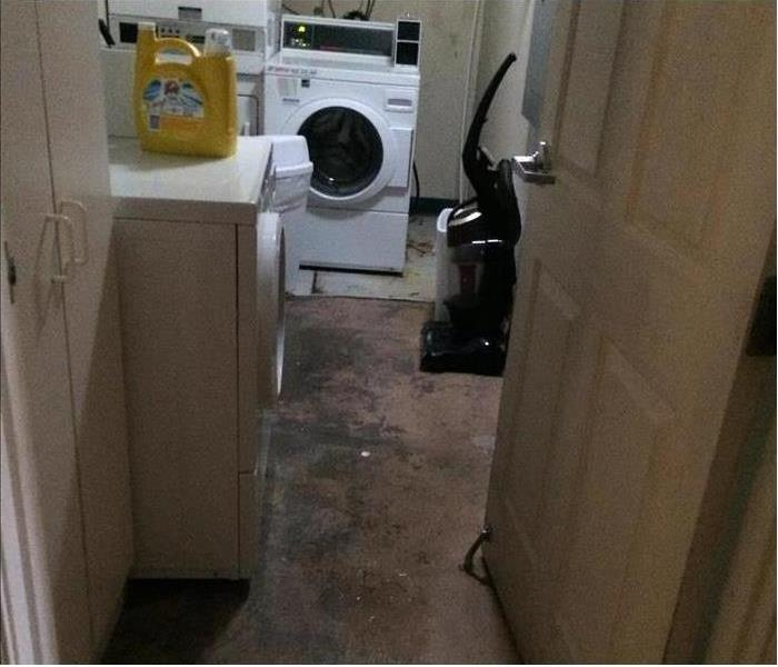 Laundry room with washing machine and dryer. Dark spots on flooring