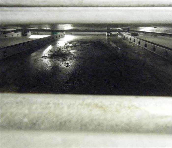 Soot and dirt under commercial refrigerator