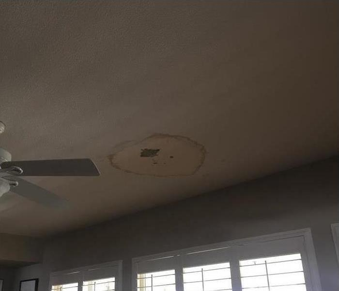 Large water stain on white ceiling. Ceiling fan on left side of the picture.