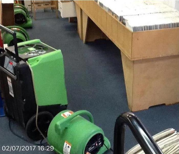Blue flooring with green SERVPRO drying equipment on it